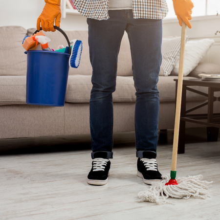 Unrecognizable man ready to clean. Crop of male legs with mop and plastic bucket with cleaning supplies standing near. Household and cleaning service background, copy space