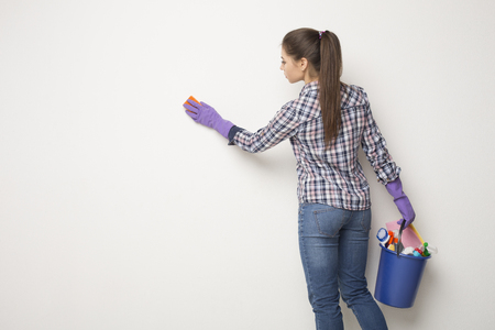 Woman wiping white wall from dust with dry rag, back view. CLeaning service or regular clean up concept, copy space Imagens