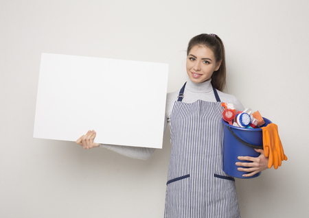 Cleaning services concept. Young woman in apron holding white banner, copy space for advertisement. Girl with bucket with detergents and rags at white isolated background, copy space