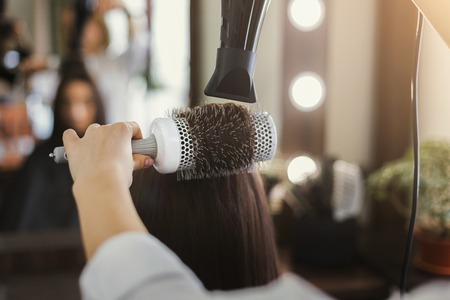 Beautician drying womans hair after giving a new haircut at salon. Beauty, care, hair cocnept