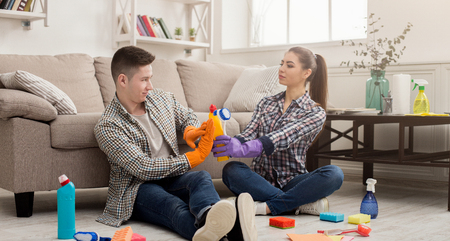 Young couple cleaning home and having fun. Woman giving denying man sponges, sitting on floor with variety of detergents copy space Imagens