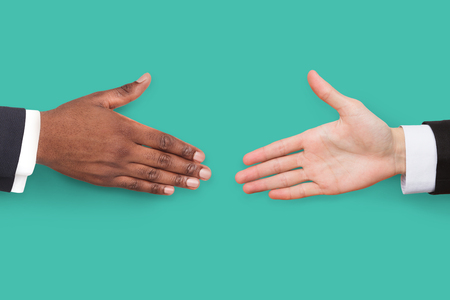 African-american and caucasian businessman hands ready for handshake on turquoise background.
