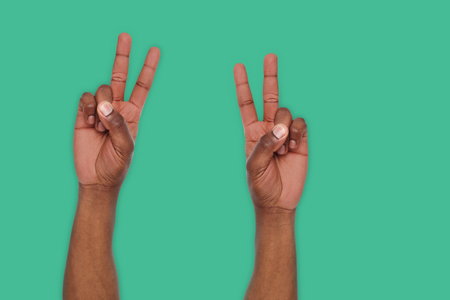 Black man hands showing victory sign or number two on turquoise background. Counting gesturing, enumeration