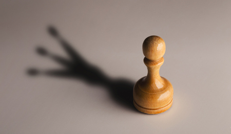 Wooden chess pawn with king shadow on gray background