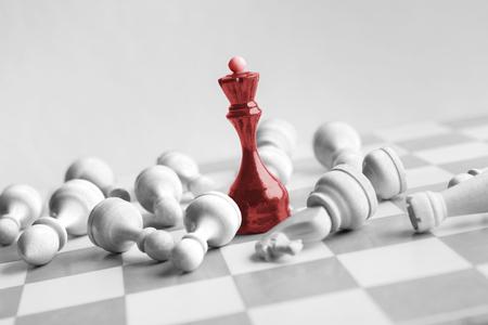 La reine d'échecs noire bat les blancs sur l'échiquier sur fond blanc. Concept de victoire et de réussite, espace de copie