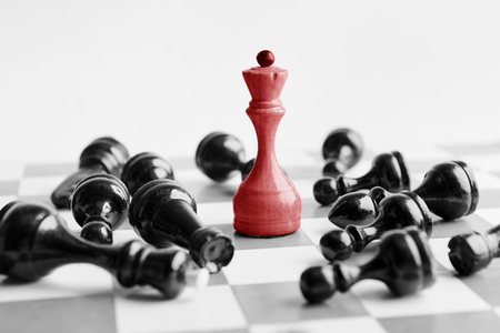 White chess queen beats blacks on chessboard over white background. Archivio Fotografico