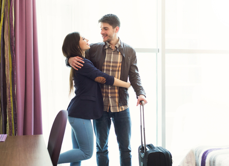 Young happy couple with luggage in hotel room. Just married man and woman arrived to resort, romantic vacation and honeymoon concept, copy space