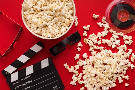 Movie background. Clapperboard, film reel, popcorn and 3D glasses on red backdrop, top view