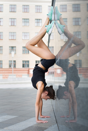 Young woman doing handstand exercise against gray wall on city street. Sporty girl practicing pilates outdoors, copy space