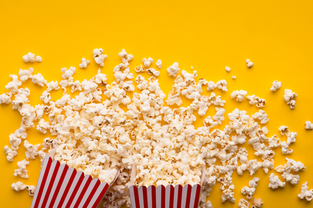 Popcorn in classic striped buckets on yellow background. Hot corn scattered from paper box, copy space. Fast food and movie snack, top view