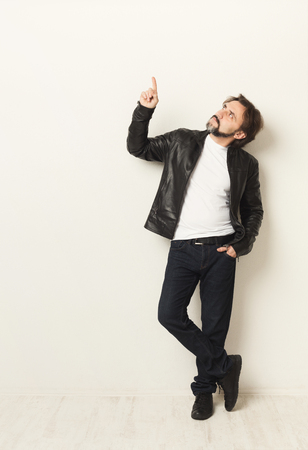 Confident casual man pointing up. Guy in leather jacket over white studio background. Advertising poster, copy space