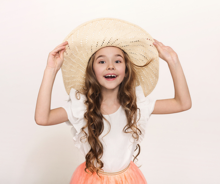 Happy little girl in straw hat at white studio background, copy space. Portrait of cute smiling child ready for summer