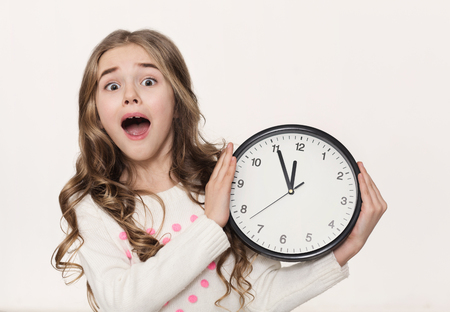 Worried little girl with clock at white studio background, copy space. Being late, time is the most precious resource concept