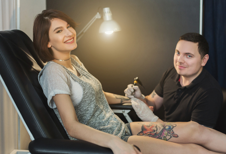 Painful tattooing process, young woman enduring pain while master making tattoo on her arm. Popular body modification, modern lifestyle, copy space