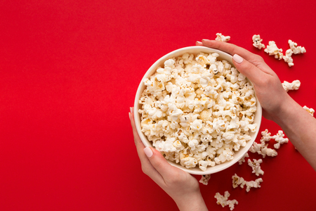 Hands holding popcorn classic striped bucket on red background. Hot corn scattered from paper box, copy space. Fast food and movie snack, top view Stock Photo