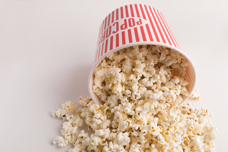 Popcorn in classic striped bucket on white background. Fluffy maise scattering from paper box, copy space. Fast food and movie snack, entertainment concept