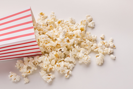 Popcorn in classic striped bucket on white background. Hot corn scattered from paper box, copy space. Fast food and movie snack Stock Photo