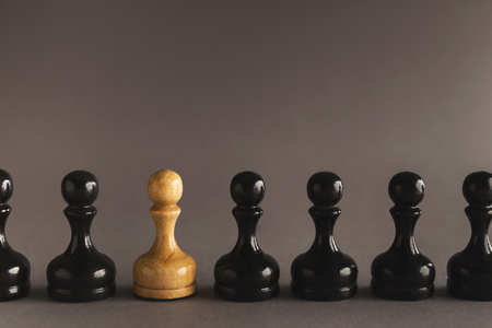 Line of black pawns with one white inside. Uniqueness of individuals in mass, loneliness concept 스톡 콘텐츠