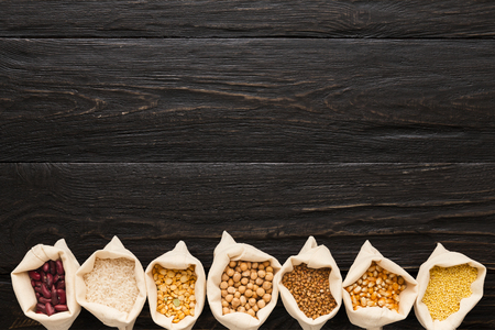 Border of assorted gluten free grains in cloth bags on rustic wooden background, copy space, top view Stock Photo
