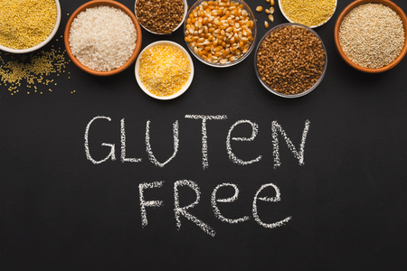 Border of assorted gluten free grains in bowls on black background, copy space, top view, chalk inscription Stock Photo