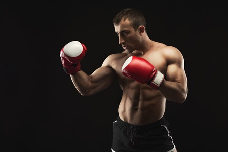 Strong muscular man in red boxing gloves at black studio background, low key, copy space