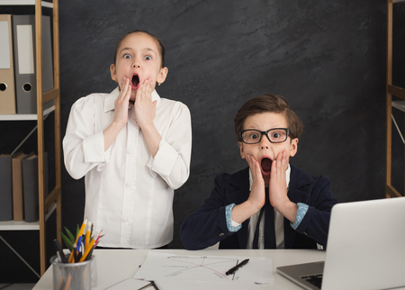 Two shocked children in office. Little boy and girl in formal wear at worktable playing adult businessmen. Startup concept