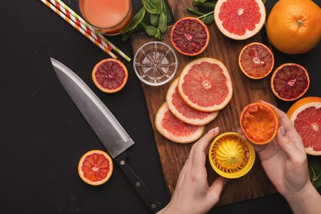 Hands making orange juice with squeezer at black background with cut citrus fruits and knife, top view, copy space