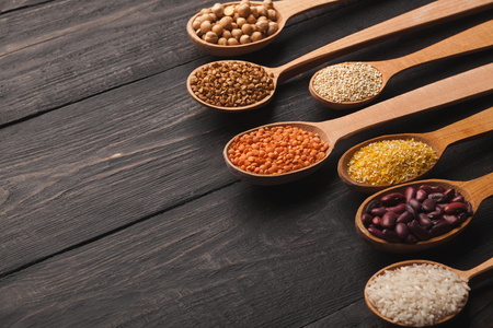Border of assorted gluten free grains in spoons on rustic wooden background, copy space