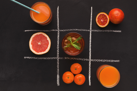 Tic-tac-toe of citrus fruits and fresh juice on black chalkboard background, top view. Healthy food concept Banco de Imagens