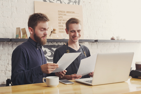 Surprised bearded barman with laptop and papers at bar counter. Boss and bartender check business report. Online purchase, technology, coffee business and service concept, copy space