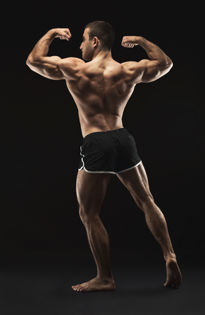 Male bodybuilder posing on black studio background. Back view of strong body and muscles, low key