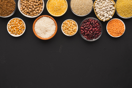 Border of assorted gluten free grains in bowls on black background, copy space, top view