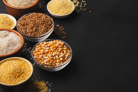 Assortment of gluten free grains in bowls on black background, copy space. Stock Photo