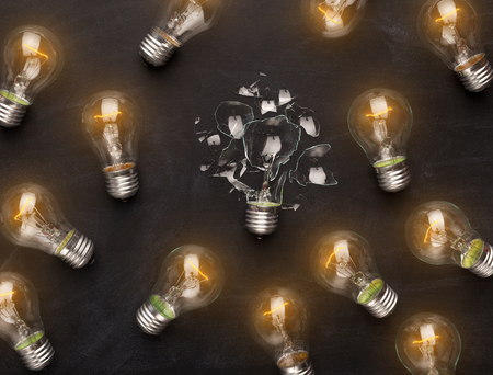 One broken light bulb among whole glowing ones on black background, top view. Creativity, idea and fragility concept