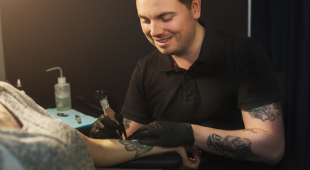 A professional tattooer artist doing picture on hand of woman by machine. Tattoo art on body. Equipment for making black ink from a jartattoo art. Archivio Fotografico