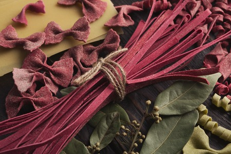 Various types of red pasta on wooden background. Naturally colored with beetroot juice italian macaroni, closeup 免版税图像