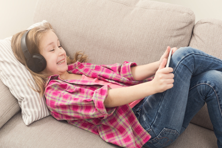 Excited little girl playing online games on smartphone and listening to music in headphones, lying on sofa at home. Modern technologies addiction and social networking concept, copy space