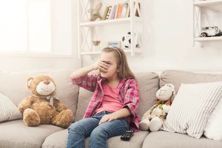 Scared little casual girl watching tv. Frightened female kid sitting on sofa with closed eyes, home alone, watching forbidden scary movies with her toy friends teddy bear and sheep, copy space