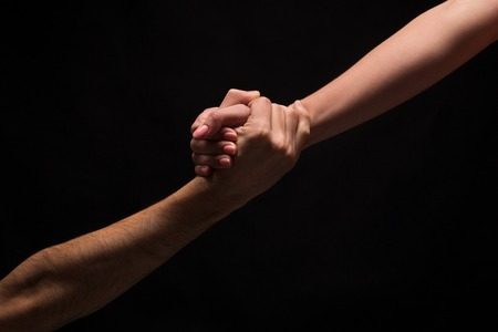 Male and female hands holding tight together on black isolated background. Love, relations, support, together forever concept. Copy space, cutout, low key Banco de Imagens