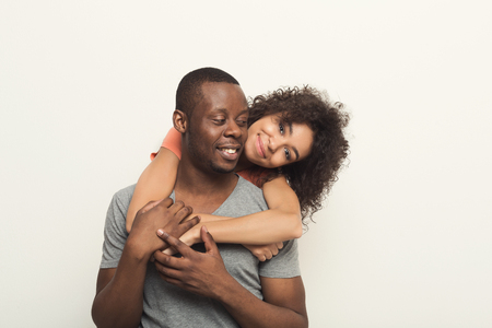 Loving black couple piggybacking. Happy young man with his girlfriend, white isolated studio background, copy space Archivio Fotografico - 102307263