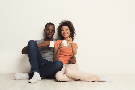 Happy african-american couple watching movie at home and drinking coffee while sitting on floor against white wall background. Cinematography and family leisure concept, copy space, isolated