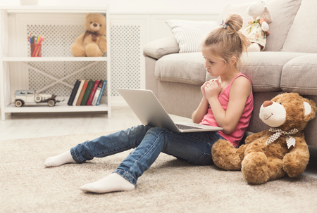 Sad little girl watching movie. Sorry female kid sitting on floor, home alone, watching cartoon on laptop with her toy friend teddy bear, child sympathy and sincerity concept, copy space