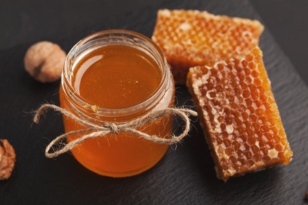 Fresh honeycombs and liquid honey in glass jar on black background, closeup