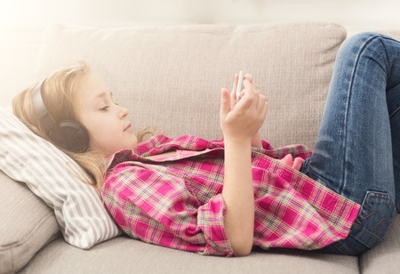 Little girl playing online games on smartphone and listening to music in headphones, lying on sofa at home. Modern technologies addiction and social networking concept, copy space Stock Photo