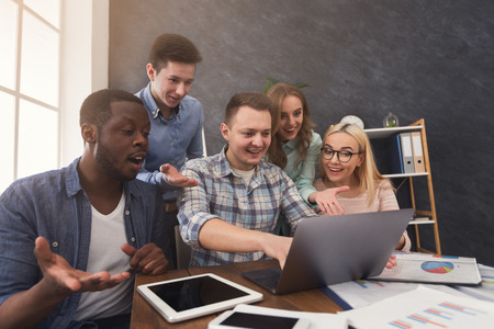 Group of shocked professional agents looking and gesturing at screen of computer, lost the tender, program error, copy space Stock Photo