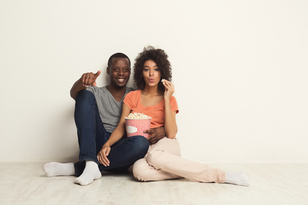 Happy african-american couple watching movie at home and eating popcorn while sitting on floor against white wall background. Cinematography and family leisure concept, copy space, isolated Foto de archivo