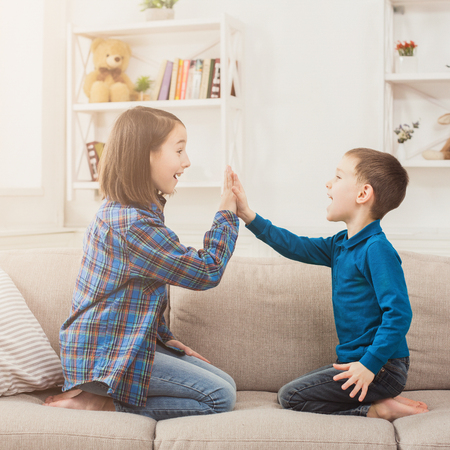 Brother and sister playing clapping hands together at home. Children game, joint activities and interests, trust, support, entertainment concept Imagens