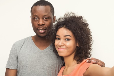 Couple selfie. Studio shot of casual african-american couple smiling at camera on white studio background, copy space, isolated