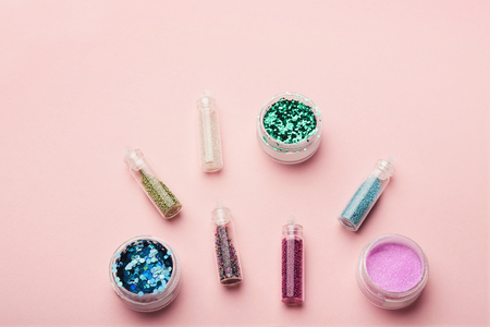 Various gritters for nail design on pink background, copy space, top view Stock Photo
