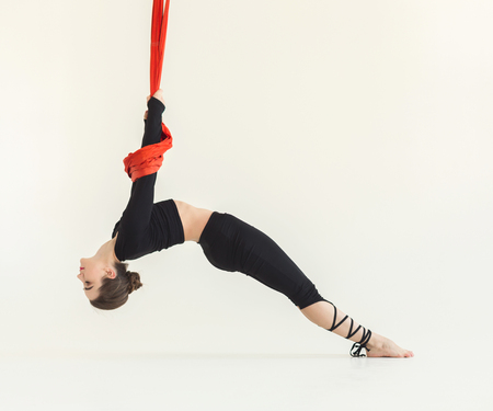 Sporty woman practicing fly yoga asana and stretching over white background in fitness gym, copy space. Health, sport, yoga concept